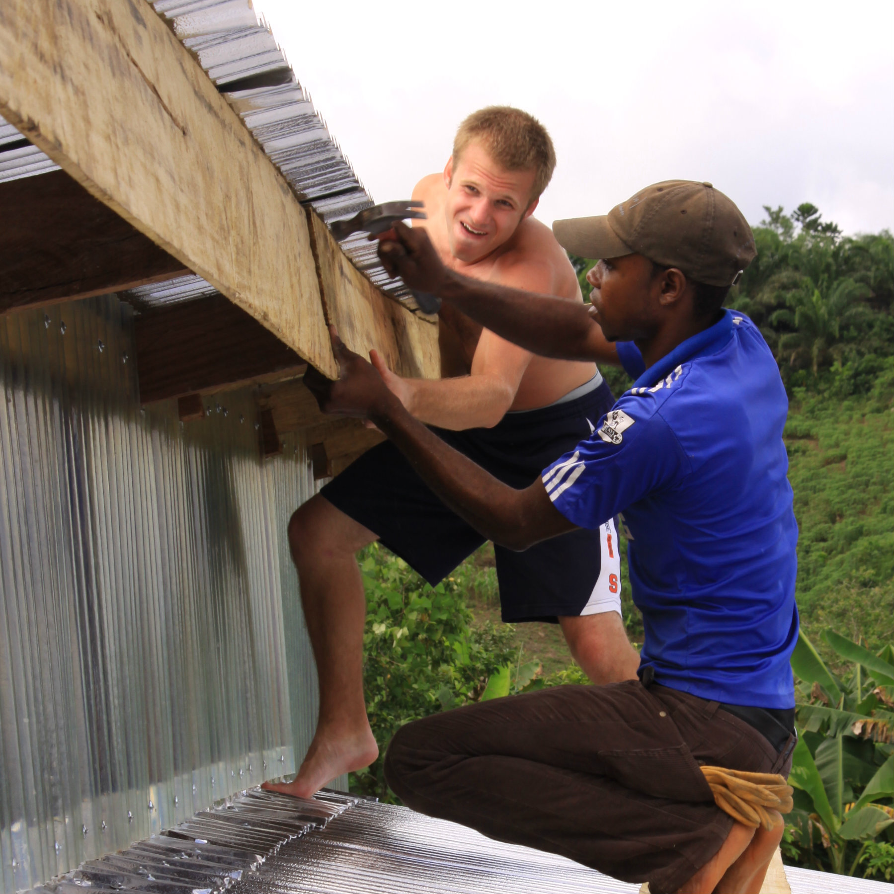 students constructing roof on building