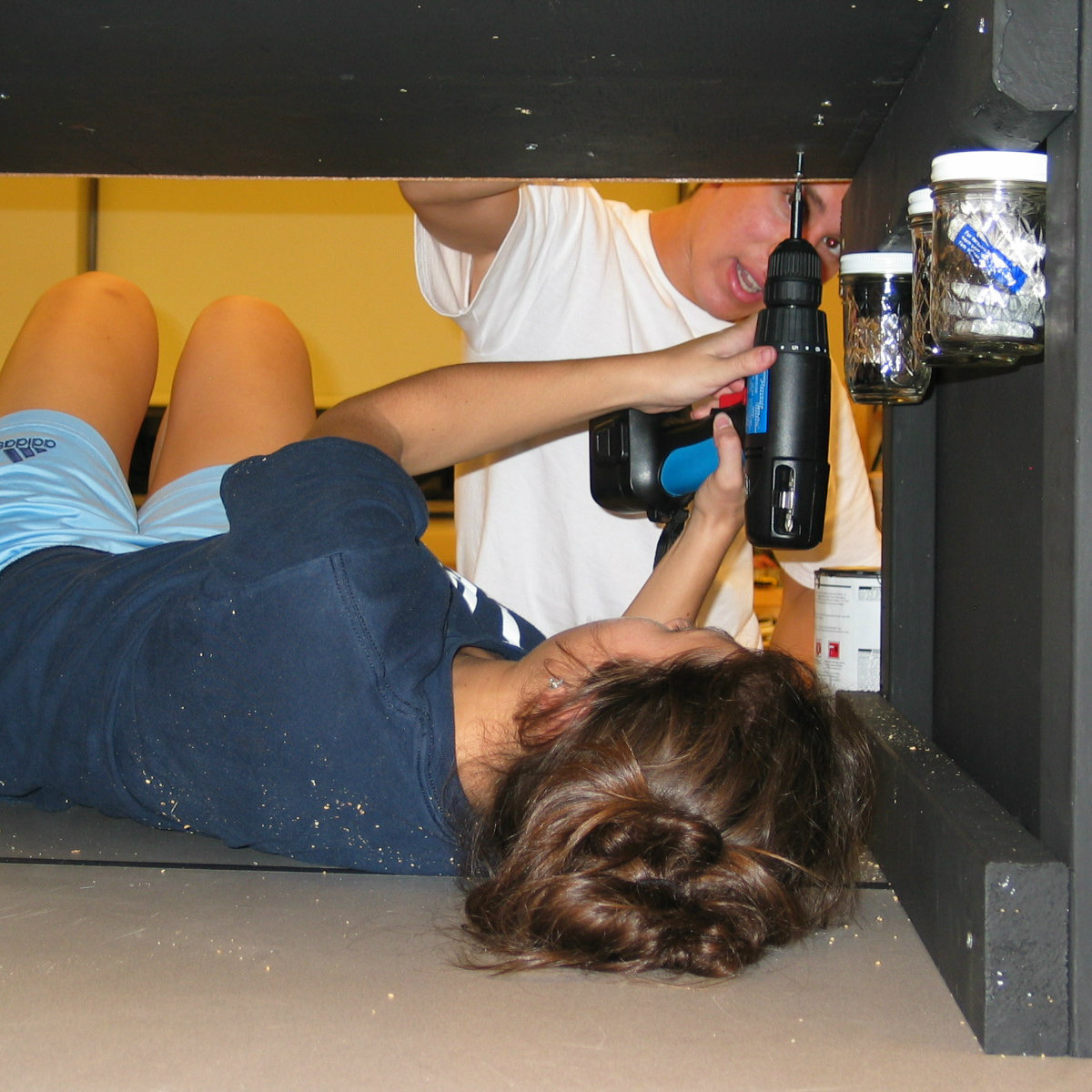 students using a drill in a tight spot under desk