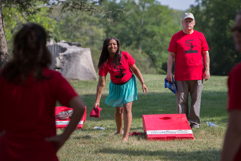 People play cornhole at the lawn party