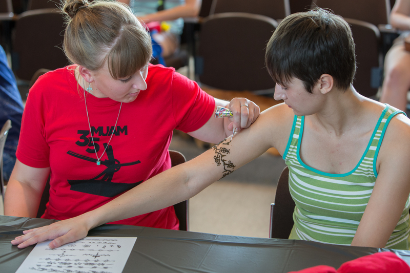 A student receives a henna tattoo on her arm