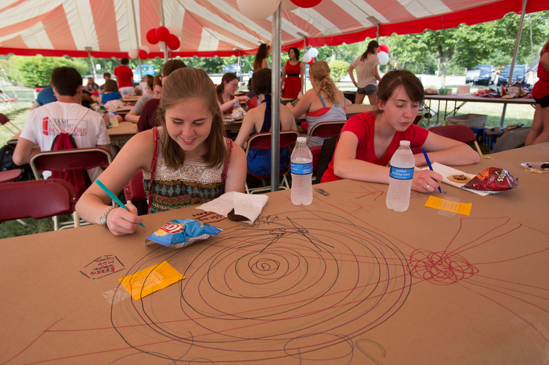 Students scribble on butcher block sheets at a table under the tent at the Lawn Party