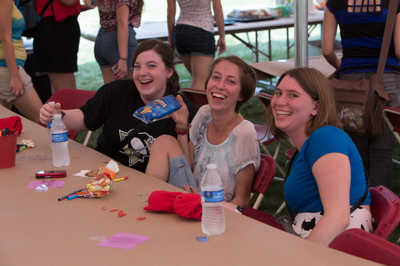 Three smiling students seated under the tent at the Lawn Party
