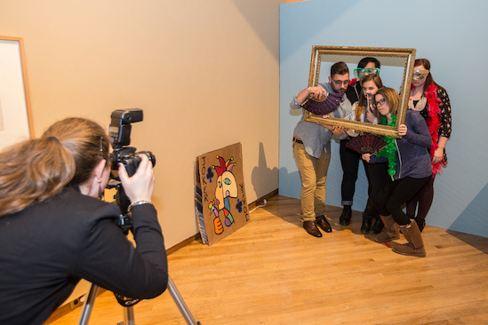 A photographer leans in for a photo of students posing behind a large rectangular open picture frame