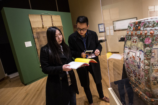 Two students stand before an artwork and consult a booklet