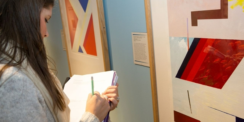 A young woman jots notes on a notebook as she stands in front of a colorful artwork