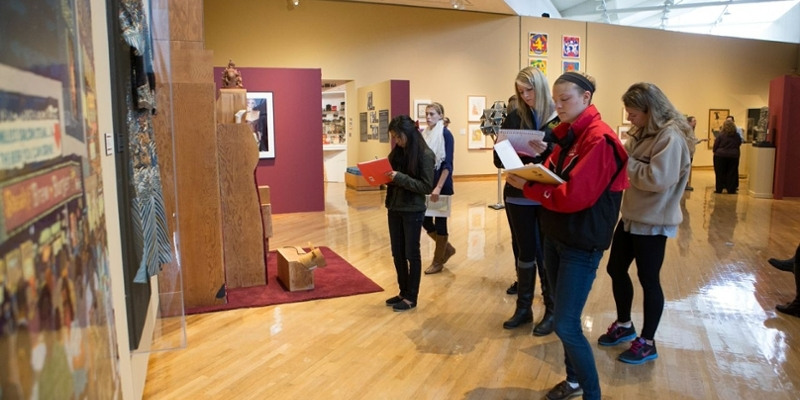 A wide view of students gathered in small groups as they take notes on artwork in the gallery
