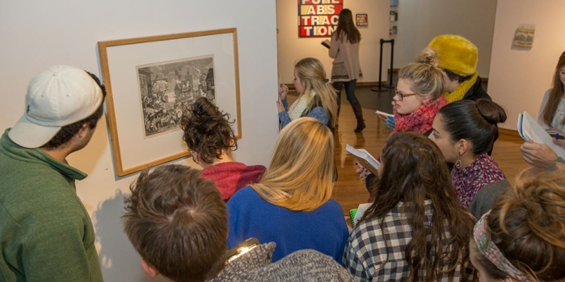 A group of students gather in front of a framed print on the gallery wall