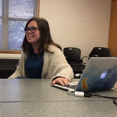 A student uses her laptop to present on her internship experiences