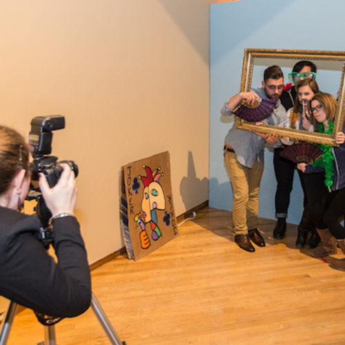 A student photographs a group of people posing behind an ornate rectangular frame