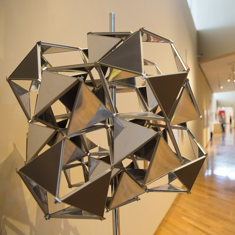 A metallic sculpture with triangle shapes is seen in the gallery, with distant figures of visitors