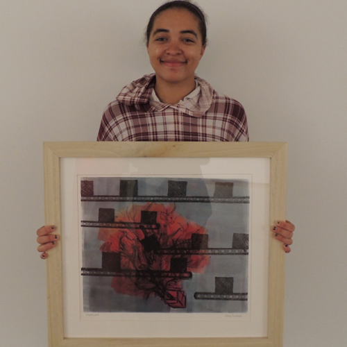Student artist Ashley Jackson holds one of her paintings