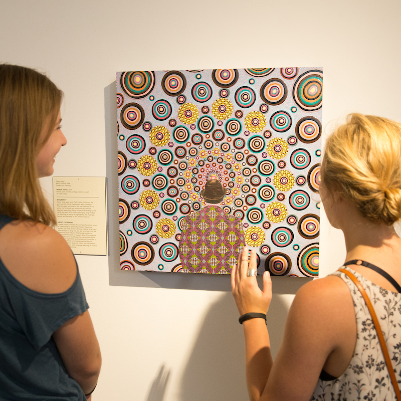2 women examine a work of art on the wall