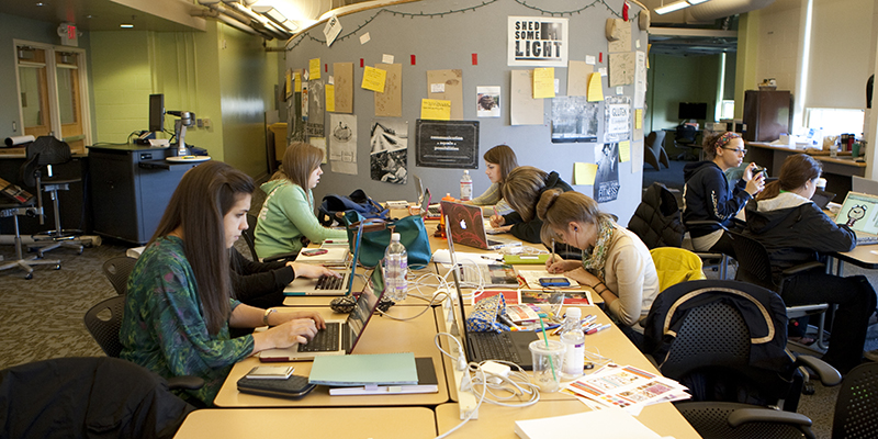 Students work at rectangular tables with printouts and laptops in the communication design studio