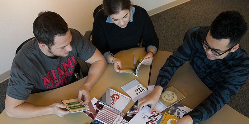 An overhead view of students working at a table with print materials during ART 251 typography class