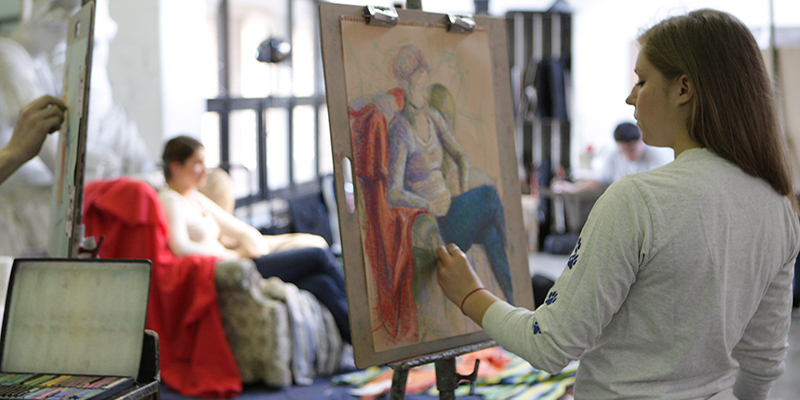 A woman seated in an armchair poses for students in the drawing studio as they sketch the scene.