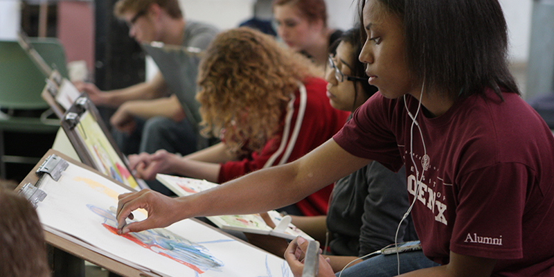 closeup of a student working on a drawing, with other classmates in background