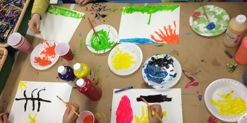 Children at a table work on watercolor paintings