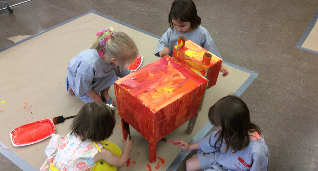 Four children paint a colorful project