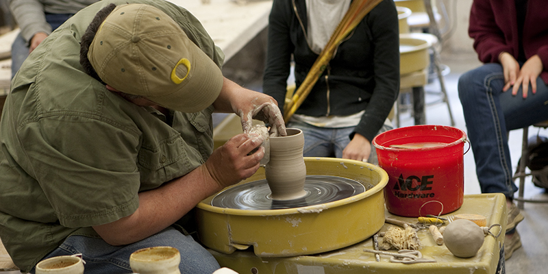A person uses a pottery wheel in Ceramics class