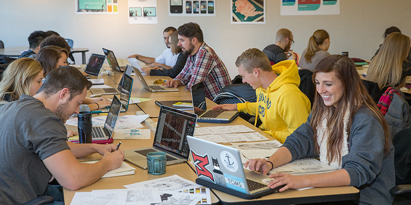 Students seated at rectangular tables work on computers during a typography class