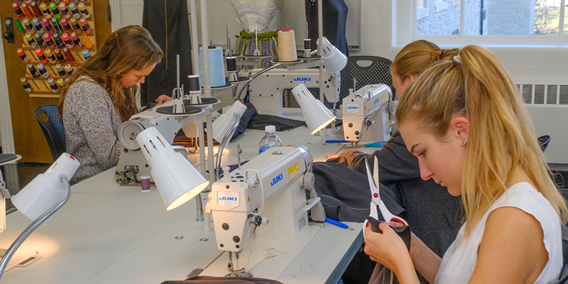 Students working at a table in the fashion design classroom