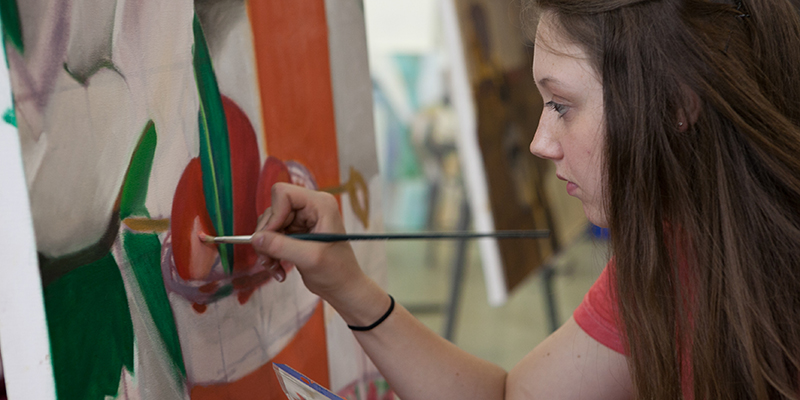 2D studio student focuses as she paints a canvas