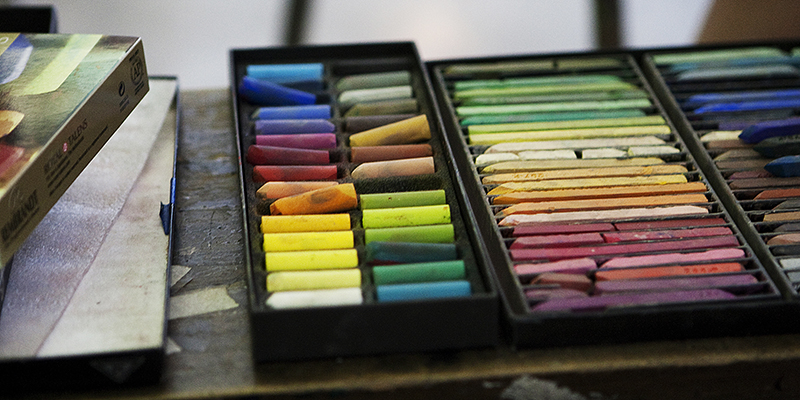 A box full of colorful pastel crayons