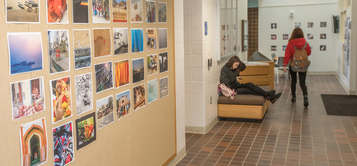 Prints are pinned to an Art Building bulletin board. Students work and walk in the hallway.