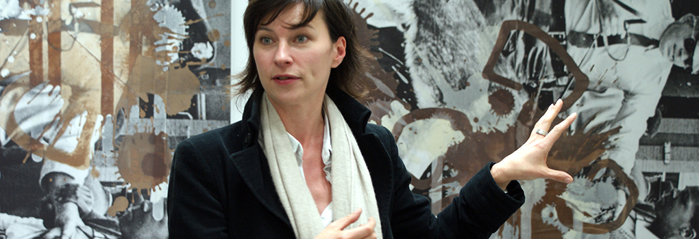 A museum curator delivering a talk as she gestures toward an artwork