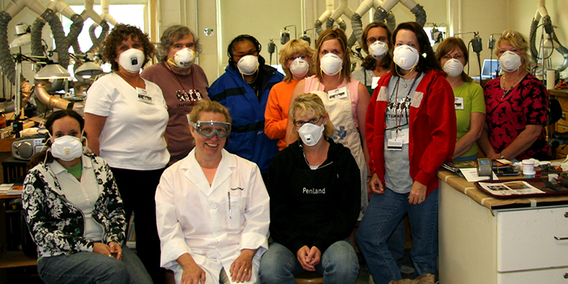 Students in an enameling studio wear face masks as they pose for a group photo