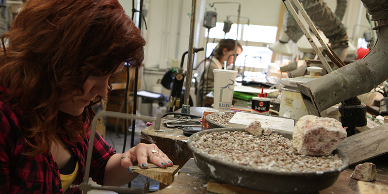 Students work on jewelry at a workbench