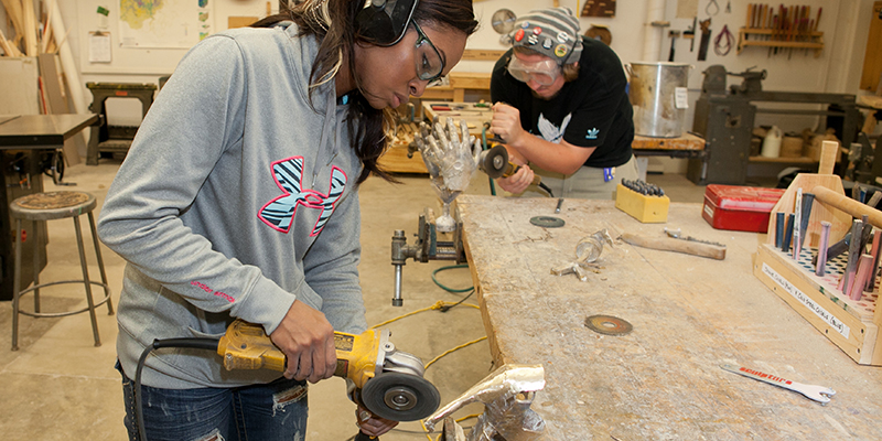 Students wearing protective gear work on shaping a sculpture