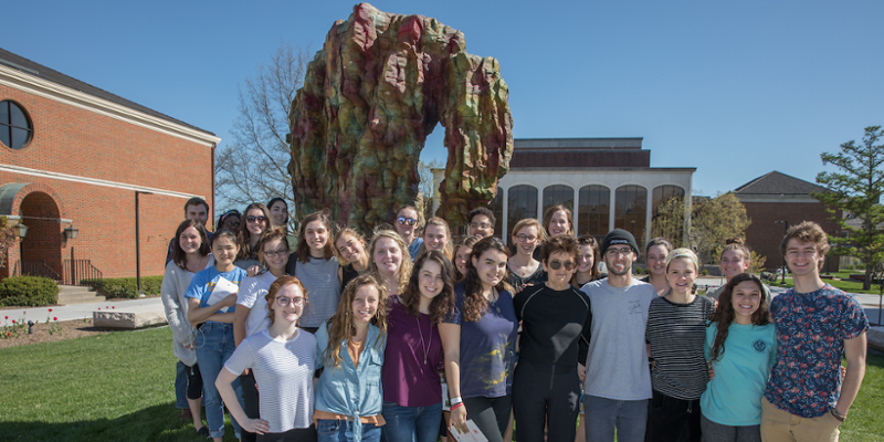 Students stand with the donor at the dedication of Hand in Heart sculpture. The fine arts plaza is visible in the background