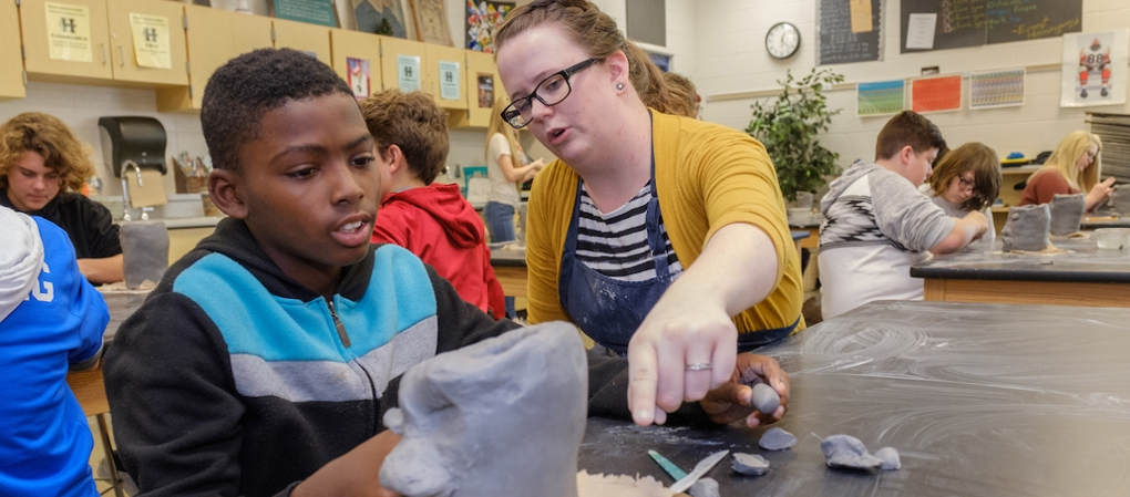 A student teacher converses with a student about an art project