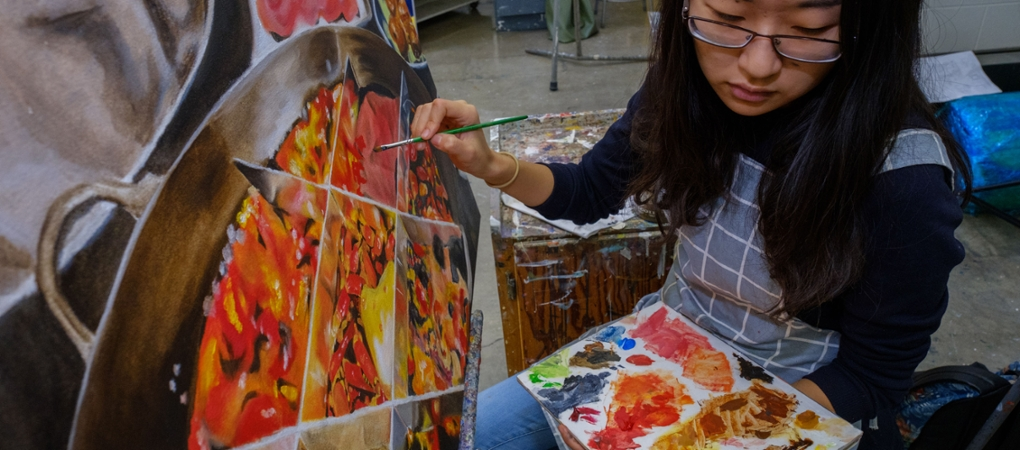 A student holding a palette looks left while working on a painting