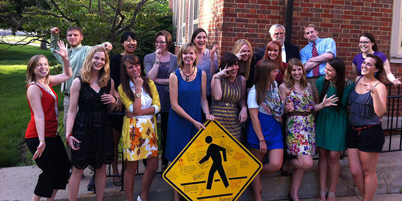 Graphic design students in AIGA and faculty strike comical poses around an autographed crosswalk sign