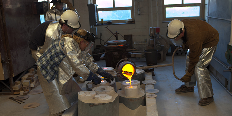 Students wearing protective gear observe a bronze pour in the studio