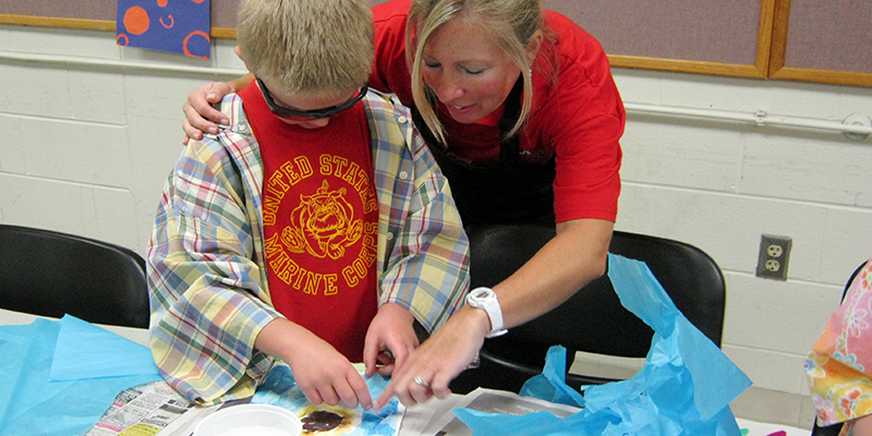 Saturday Art teacher helps child with art project