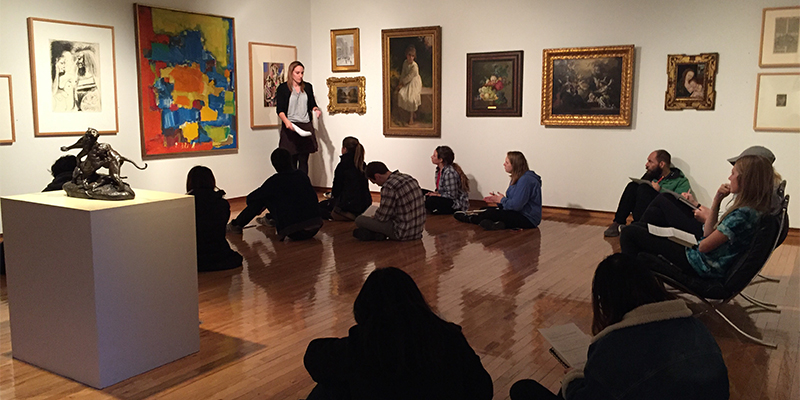 A group of students seated in a gallery as a professor speaks before a group of paintings