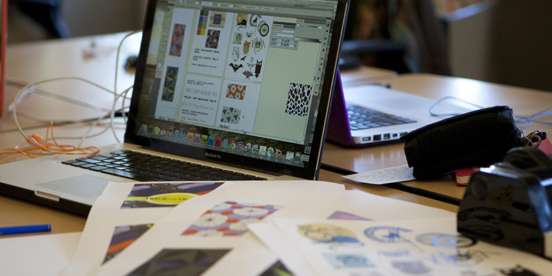 A laptop is open with the screen showing colorful graphic elements. Assorted printed graphic design materials are scattered on the table.