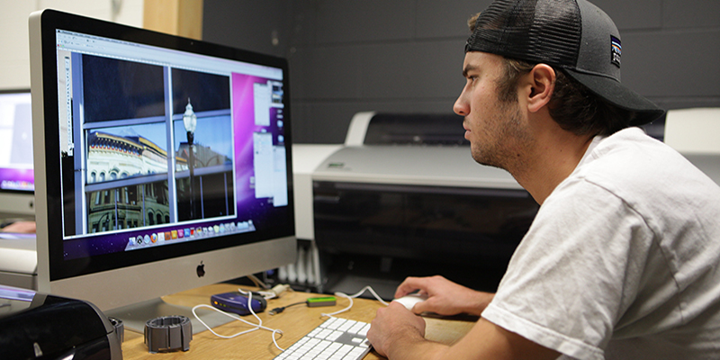 A digital photography student uses software to edit an image on a computer