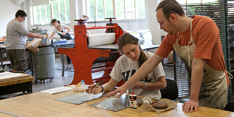 A graduate student directs a student in the printmaking studio while two other students work across the room