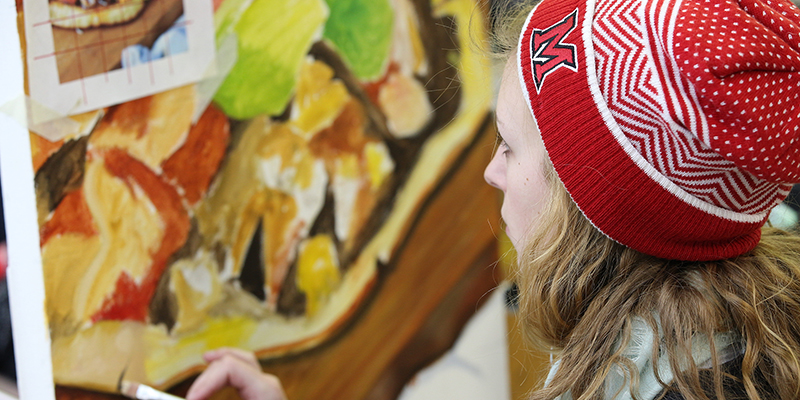 A student participates in a painting class