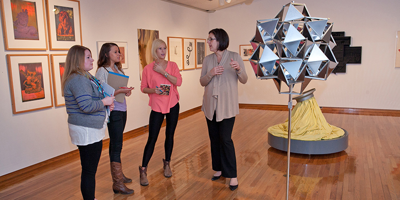 A group of students listen as a professor speaks in front of a silver geometric sculpture