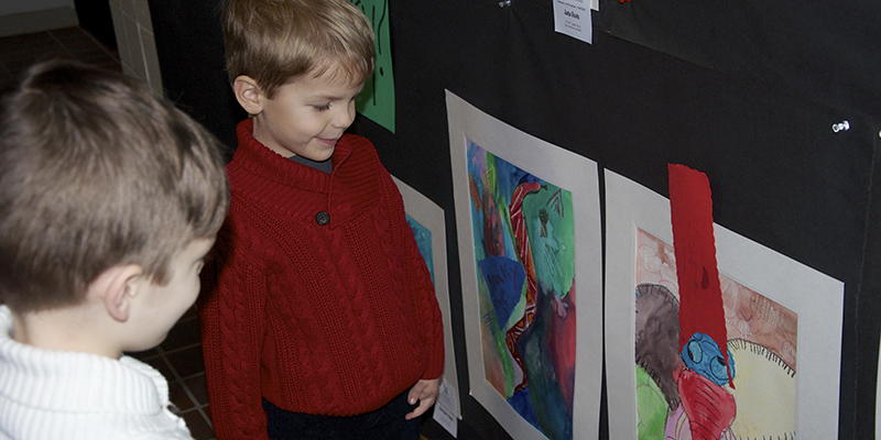 Two children admire artwork in a Saturday Art exhibition