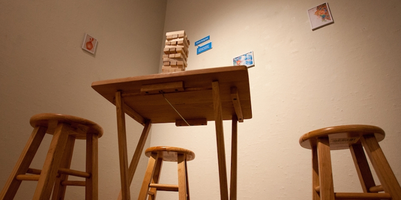 An installation of stools, a table, and a stack of slotted wooden blocks