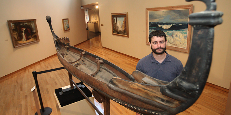 A student stands near a model of an ancient boat in the Miami Art Museum