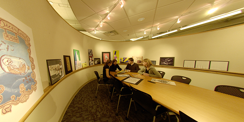 Students work together at a table in the graphics studio