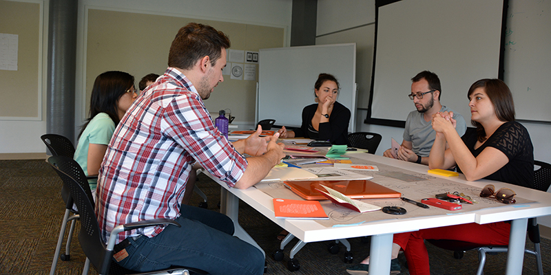 Experience Design students meet around a table, with materials spread around them.