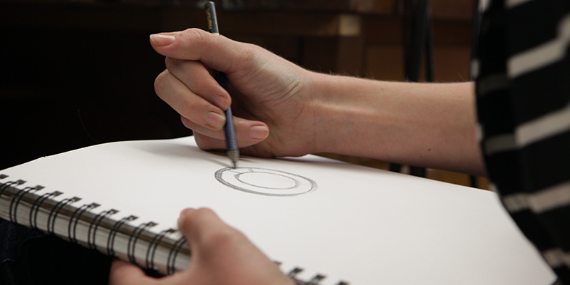 Student drawing in a sketchbook